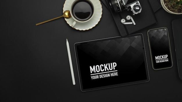 Widok z góry na czarny stół z tabletem, smartfonem, filiżanką kawy i makietą aparatu