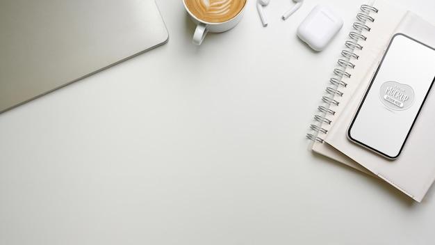 Widok z góry na kreatywne biurko z makietą smartfona, notebookami, laptopem i materiałami eksploatacyjnymi