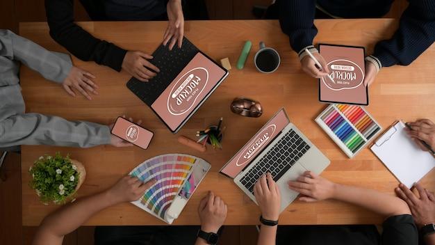 Widok z góry na odprawę zespołu projektantów na temat ich projektu z makietą urządzeń
