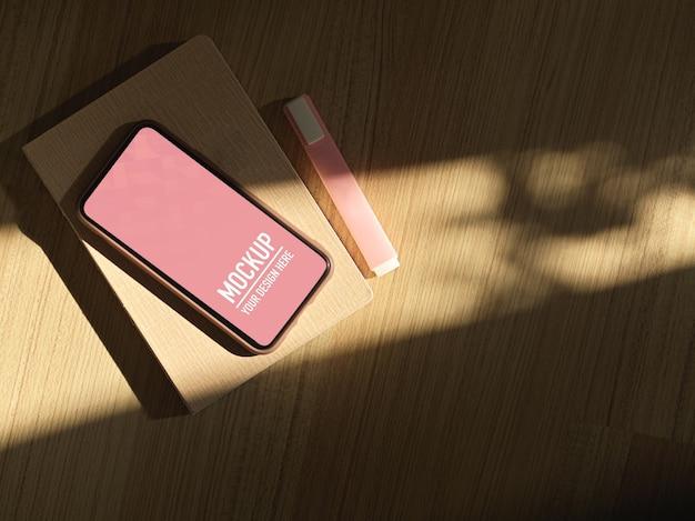 Widok z góry na smartfon, notatnik, marker i światła słoneczne na stole