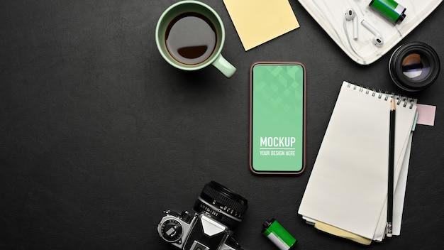Widok z góry obszaru roboczego z makietą smartfona, kubkiem do kawy, aparatem, materiałami eksploatacyjnymi na czarnym stole