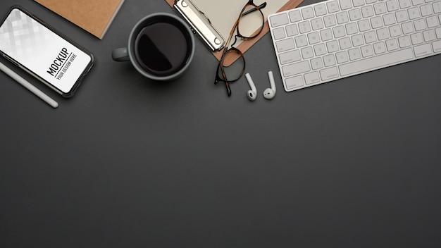 Widok z góry obszaru roboczego z materiałami eksploatacyjnymi i makietą smartfona