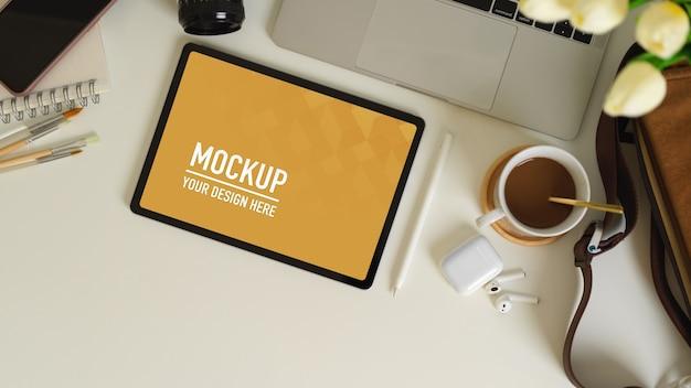 Widok z góry obszaru roboczego z tabletem, laptopem, akcesoriami i materiałami eksploatacyjnymi na białym stole