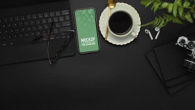 Widok z góry obszaru roboczego ze smartfonem, klawiaturą, aparatem, filiżanką kawy i makietą materiałów eksploatacyjnych