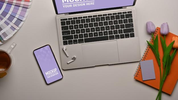 Widok z góry obszaru roboczego ze smartfonem, makietą laptopa i kwiatem ozdobionym na stole
