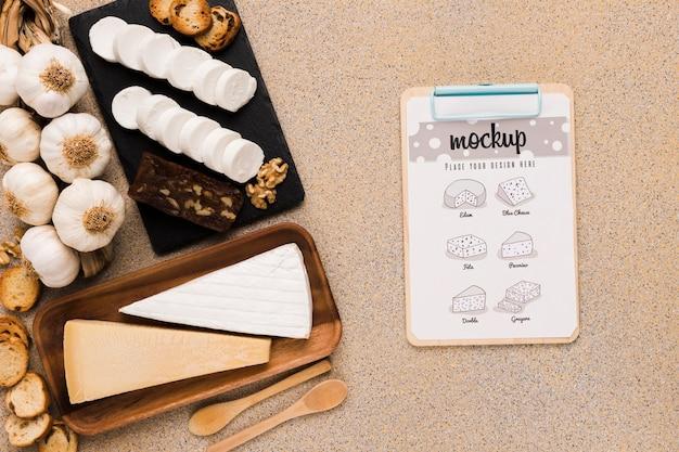 Widok z góry różnych serów z łyżkami i notatnikiem
