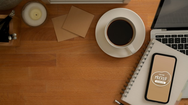 Widok z góry stołu roboczego z makietą smartfona, laptopa, filiżanki kawy, papeterii i miejsca na kopię