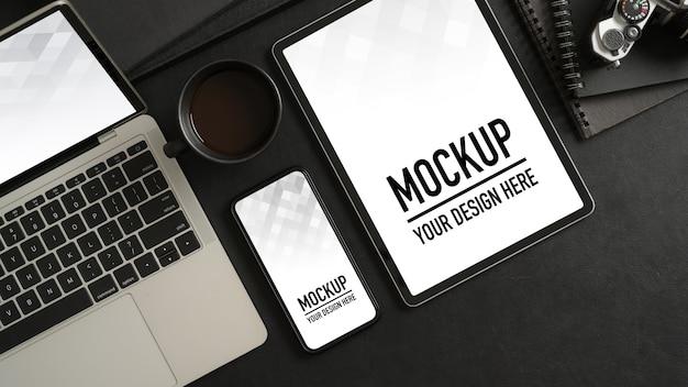 Widok z góry stołu roboczego z makietą smartfona, laptopa, tabletu, materiałów biurowych i miejsca na kopię