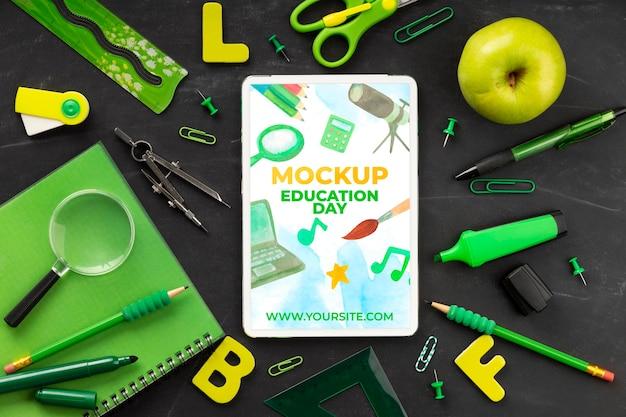 Widok z góry tabletu z podstawowymi artykułami szkolnymi i jabłkiem na dzień edukacji