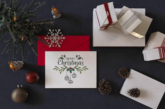 Widok z góry wesołych świąt bożego narodzenia makieta z życzeniami z dekoracją świąteczną, czerwoną kopertą i prezentami
