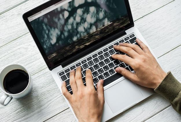 Widok z lotu ptaka mężczyzna używa komputerowego laptop na drewnianym stole