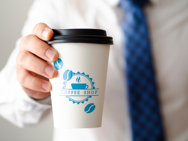 Widok z przodu człowiek trzyma makiety filiżankę kawy