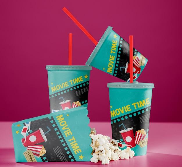 Widok z przodu kubków kinowych ze słomkami i popcornem