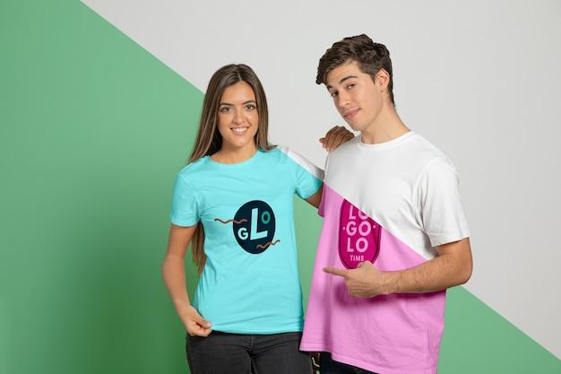 Widok z przodu mężczyzny i kobiety, pozowanie w koszulkach i wskazując na nich