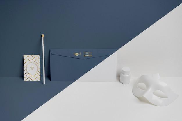 Widok z przodu minimalistycznego zaproszenia na karnawał w kopercie z maską i pędzlem