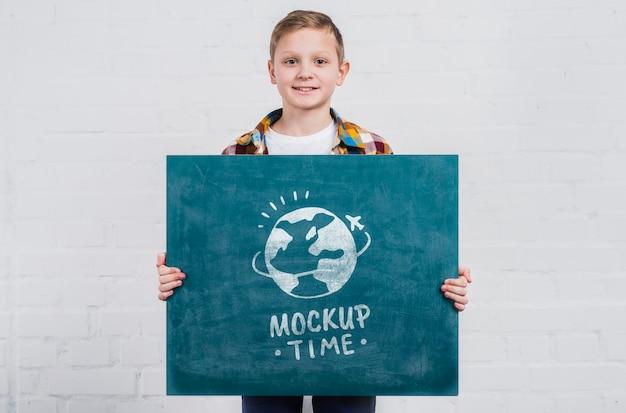 Widok z przodu młody chłopak trzymając znak makiety
