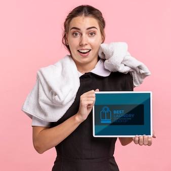 Widok z przodu pokojówka z ręcznikiem trzymając makietę tabletu