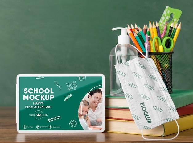 Widok z przodu tabletu z podstawowymi artykułami szkolnymi i maską medyczną na dzień edukacji