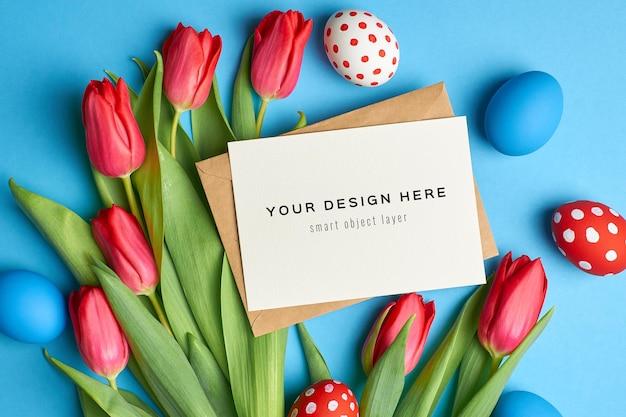 Wielkanocna świąteczna kartka okolicznościowa makieta z kolorowymi jajkami i czerwonymi kwiatami tulipanów