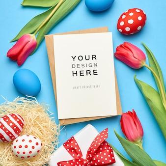 Wielkanocna świąteczna kartka okolicznościowa makieta z kolorowymi jajkami, pudełkiem na prezent i czerwonymi kwiatami tulipanów