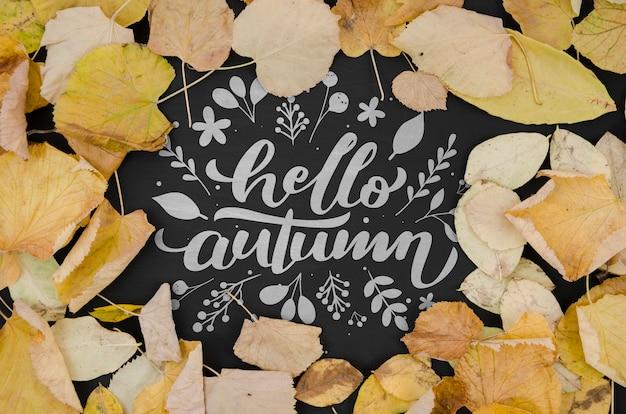 Witam jesień napis otoczony żółtymi liśćmi