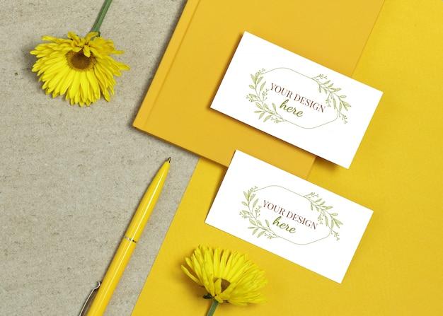 Wizytówka makieta z książki, żółty długopis i kwiaty letnie