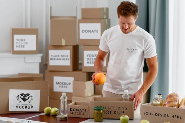 Wolontariusz przygotowuje pudełko na datki z prowiantem