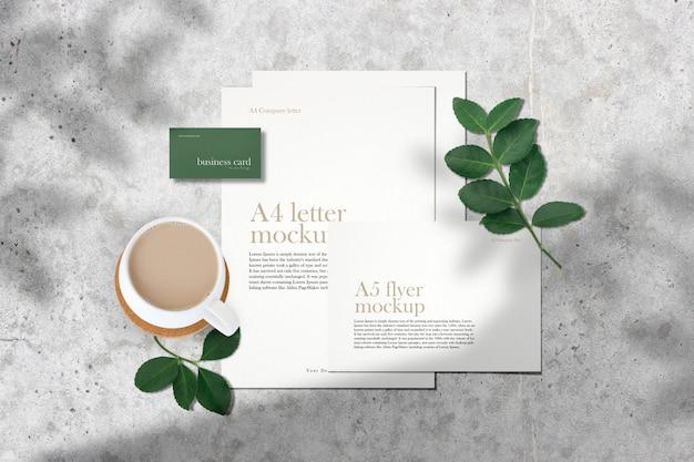 Wyczyść minimalną makietę dokumentów korporacyjnych na szarym stole z zielonymi liśćmi w cieniu.