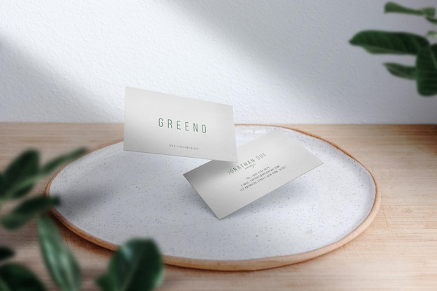 Wyczyść minimalną makietę wizytówki na białym talerzu z liśćmi