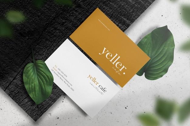 Wyczyść minimalną makietę wizytówki na czarnym drewnie z zielonymi liśćmi i lekkim cieniem.