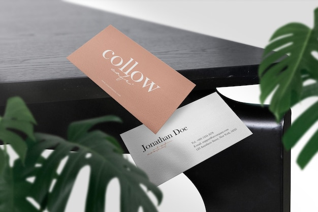 Wyczyść minimalną makietę wizytówki na czarnym stole z zielonymi liśćmi