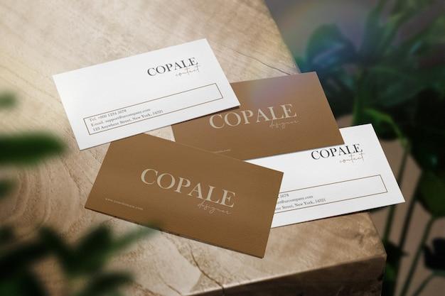Wyczyść minimalną makietę wizytówki na drewnianym stole i świetle rianbow z liśćmi.