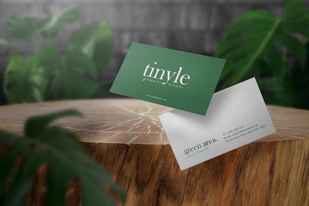 Wyczyść minimalną makietę wizytówki na drewnie z zielonymi liśćmi