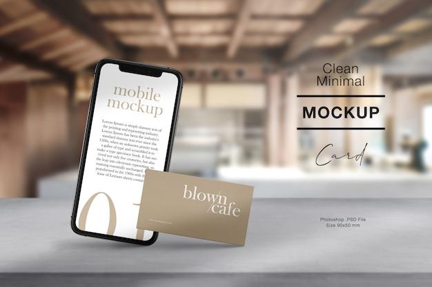 Wyczyść minimalną wizytówkę i mobilną makietę na cementowym stole z lekkim cieniem.
