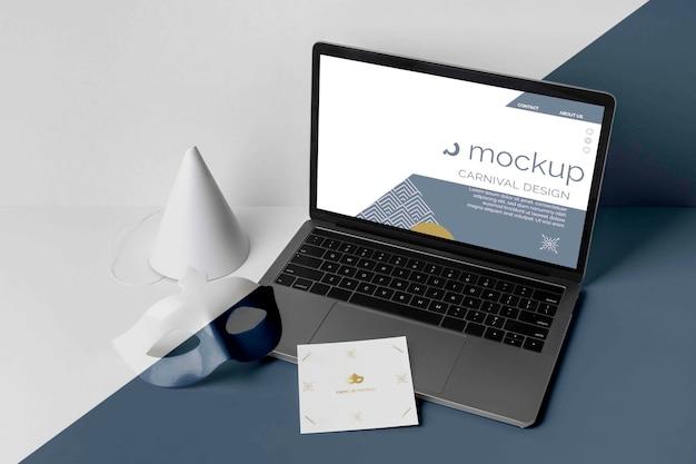 Wysoki kąt minimalistycznego zaproszenia na karnawał z laptopem i maską