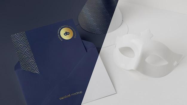 Wysoki kąt zaproszenia na karnawał w kopercie z maską i stożkiem