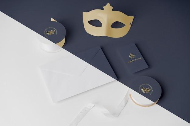 Wysoki kąt zaproszenia na karnawał w kopercie z taśmą i maską
