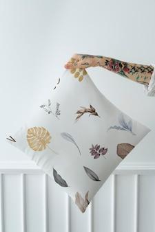 Wytatuowana kobieta trzymająca makietę liściastej poduszki