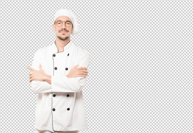 Zadowolony młody szef kuchni z skrzyżowanymi rękami gest