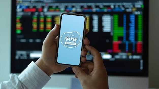 Zamknąć widok pracownika biurowego płci męskiej trzymając makiety smartfona siedząc przy biurku