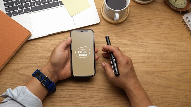 Zamknij się biznesmen trzymając smartfon i pióro w ręku na drewnianym obszarze roboczym