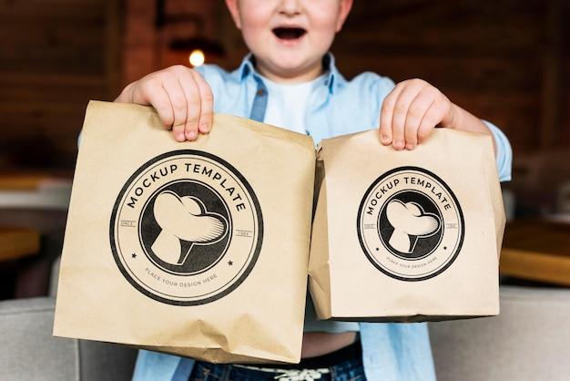 Zamknij się chłopiec trzymający torby z jedzeniem