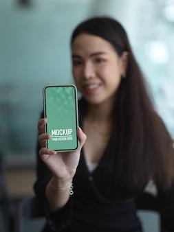 Zamknij widok bizneswoman pokazuje makiety ekran smartfona w biurze