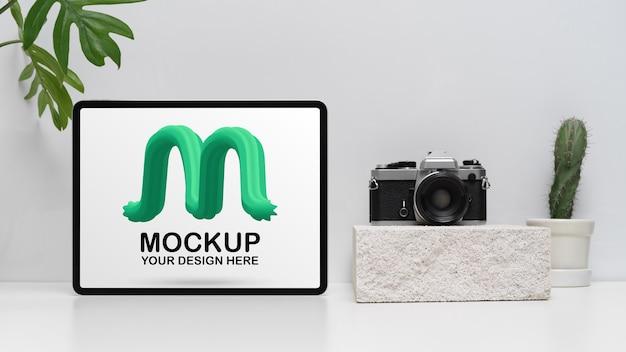 Zamknij widok makiety cyfrowego tabletu na białym stole z aparatem i dekoracjami w salonie