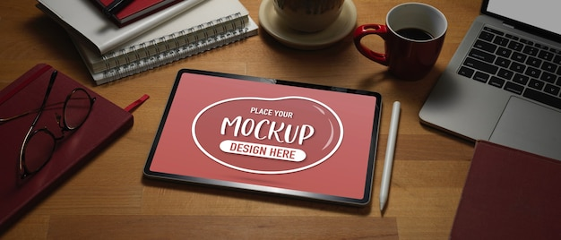 Zamknij widok makiety cyfrowego tabletu na drewnianym stole roboczym z laptopem i materiałami eksploatacyjnymi