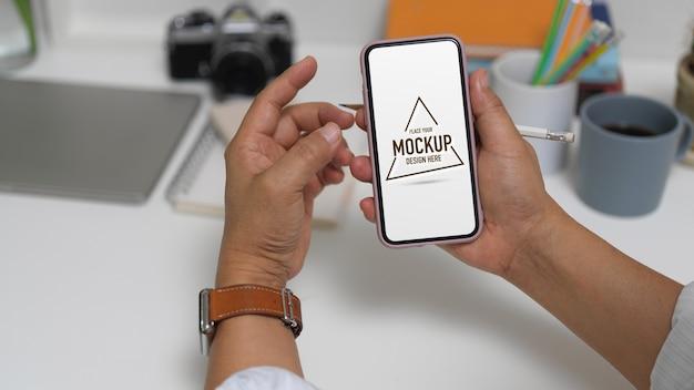 Zamknij widok męskiego przedsiębiorcy pokazując makiety ekranu smartfona siedząc w miejscu pracy