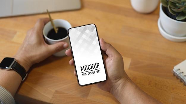 Zamknij widok męskiej ręki trzymającej makieta smartfona i filiżankę kawy na drewnianym stole