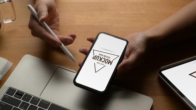 Zamknij widok mężczyzna pokazano makiety ekran smartfona podczas pracy z laptopem na biurku