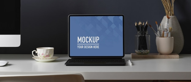 Zamknij widok stołu roboczego z makietą tabletu, papeterią i urządzeniem komputerowym