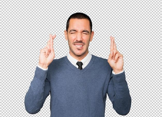 Zaniepokojony młody człowiek robi gest skrzyżowanych palców